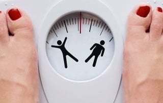 Женщина измеряет свой вес. Эффективное лечение ожирения