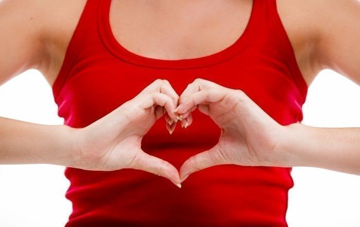 Лечение сердца и сосудов в Париже. Девушка делает форму сердца пальцами рук. Фото